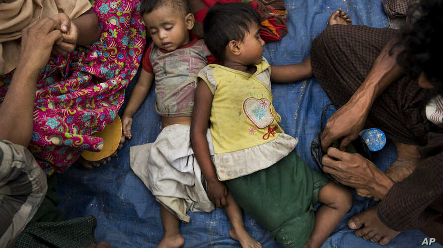 Two children sleep as Rohingya Muslims who have fled persecution in Myanmar wait along the border for permission to move further towards refugee camps near Palong Khali, Bangladesh, Nov. 2, 2017.