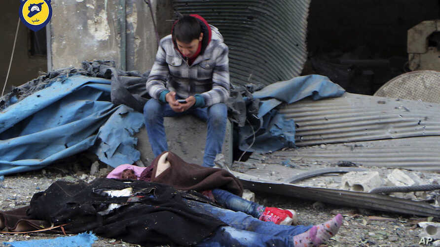 This photo provided by the Syrian Civil Defense White Helmets, which has been authenticated based on its contents and other AP reporting, shows a Syrian boy sitting next to bodies after artillery fire struck the Jub al-Quba district in Aleppo, Syria,...