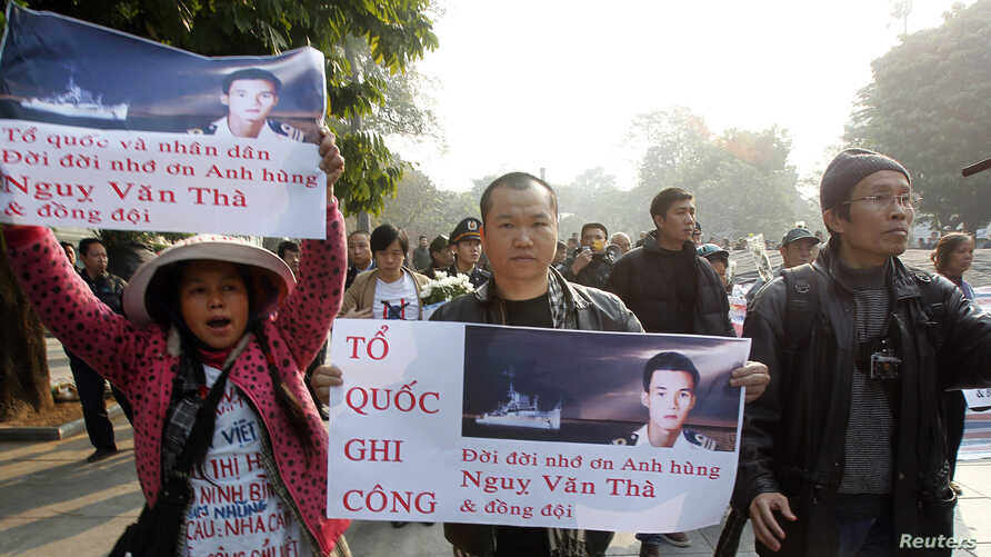 Anti-China protester Le Hoang (C) walks with a poster bearing an image of South Vietnamese naval captain Nguy Van Tha, who was killed during a naval clash with China at the Paracels islands, during a gathering to mark the 40th anniversary of the Chin