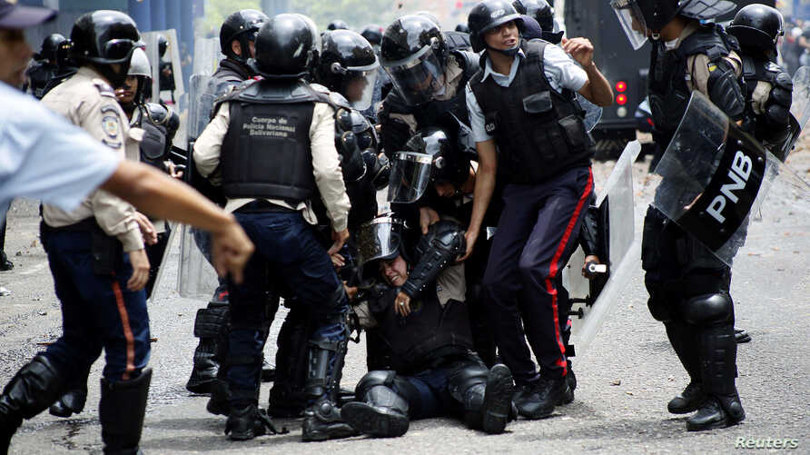 Police help an injured colleague during clashes with opposition supporters during protests against unpopular leftist President Nicolas Maduro in San Cristobal, Venezuela, April 19, 2017.