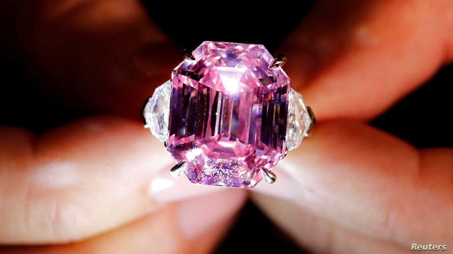 A Christie's staff holds a 18.96-carat Fancy Vivid Pink Diamond during a preview in Geneva, Nov. 8, 2018.