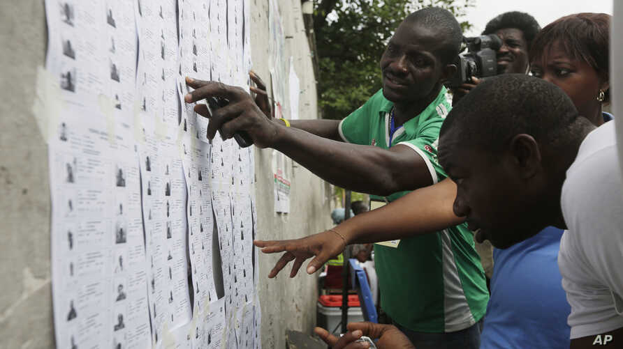 Nigerian people look for their names before they register to vote in Lagos, Nigeria, April 11, 2015.