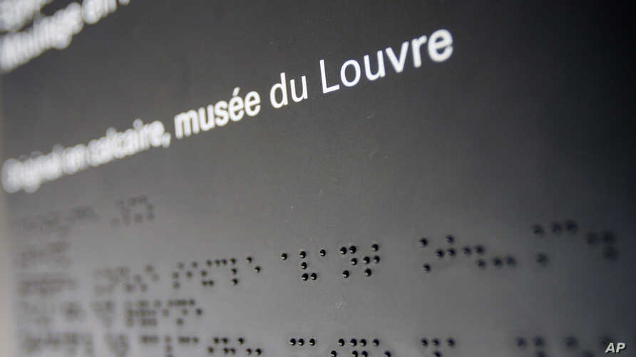 FILE - A text translated in Braille is displayed in an exhibition for blind and visually-impaired people at Louvre Museum in Paris.