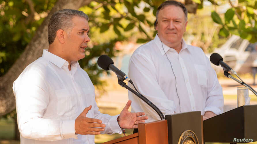Colombian President Ivan Duque speaks as U.S. Secretary of State Mike Pompeo listens during a news conference  at the guesthouse in Cartagena,  Colombia, Jan. 2, 2019.