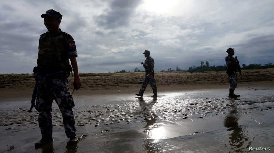 FILE PHOTO: A Myanmar border guard police officers stand guard in Buthidaung, northern Rakhine state, Myanmar July 13, 2017.