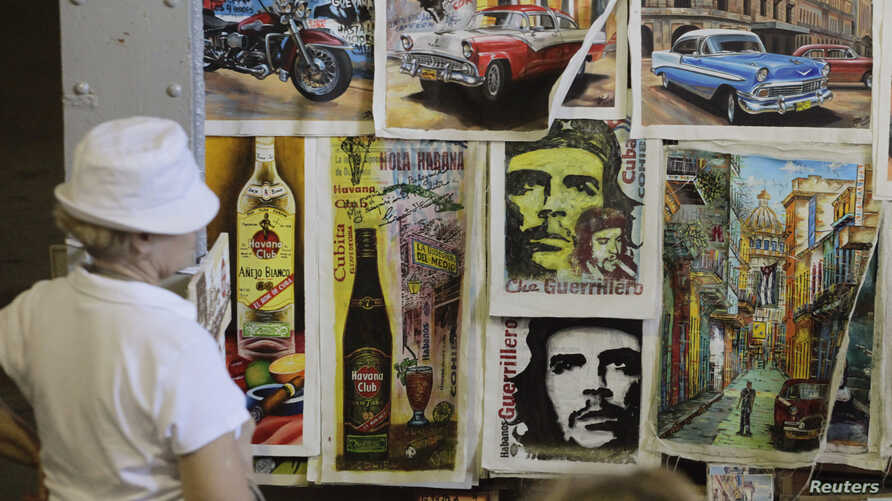 Tourists look at artwork based on images of revolutionary leader Che Guevara at an artisans' fair in Havana, Cuba, Oct. 8, 2013.