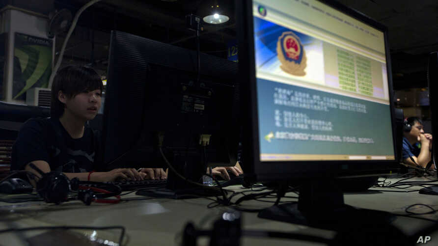 FILE - computer users sit near a display with a message from the Chinese police on the proper use of the internet at an internet cafe in Beijing, China.