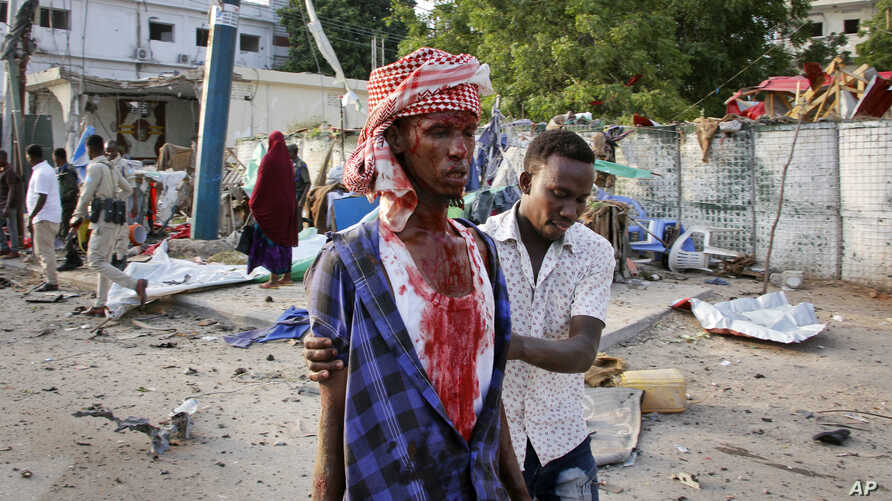 A Somali helps an injured civilian who was wounded in a bomb blast near the Sahafi hotel in the capital Mogadishu, Somalia, Nov. 9, 2018.