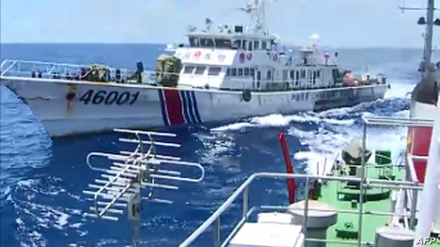 FILE - Screen grab shows the Chinese Coast Guard ship 46001 (L) chasing a Vietnamese vessel near to the site of the Chinese oil rig in the disputed waters in the South China Sea, off Vietnam's central coast.
