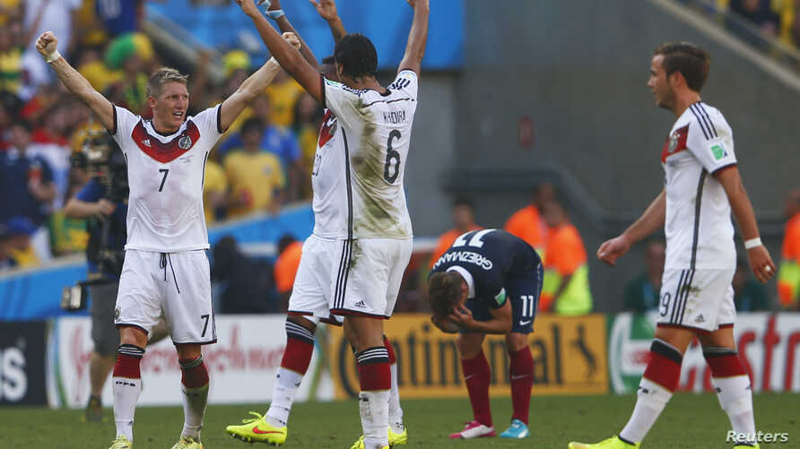 German soccer players celebrate win as France's Antoine Griezmann reacts after the final whistle is blown at 2014 World Cup quarter-finals, Maracana stadium, Rio de Janeiro, July 4, 2014.
