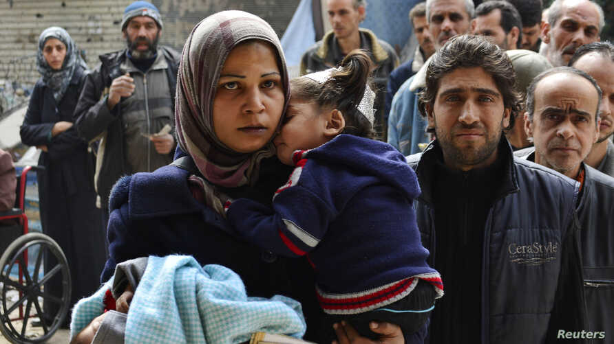 Residents line up to receive humanitarian aid at the Palestinian refugee camp of Yarmouk, in Damascus, Syria, March 11, 2015.