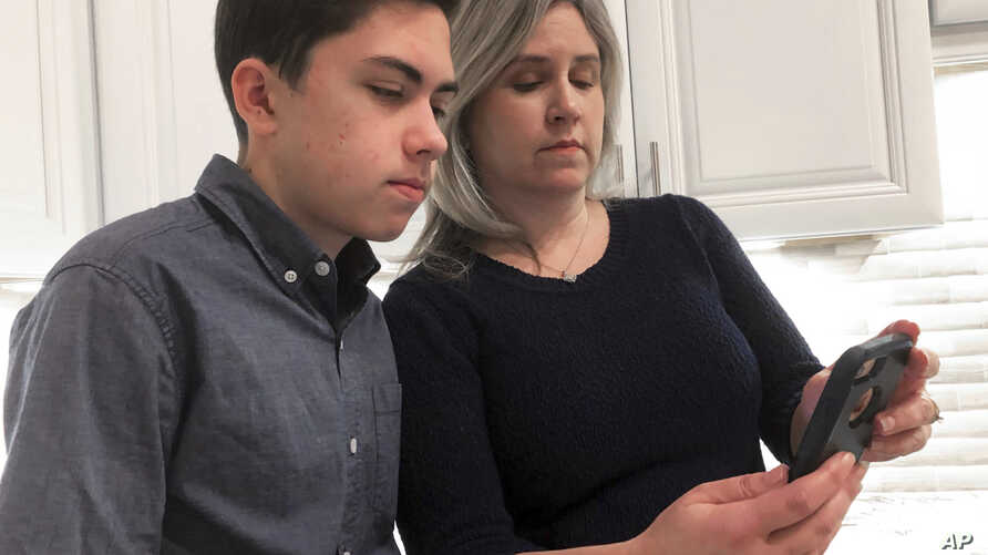 FILE- Grant Thompson and his mother, Michele, look at an iPhone in the family's kitchen in Tucson, Ariz., Jan. 31, 2019. Apple has released an iPhone update to fix a FaceTime flaw that allowed people to eavesdrop on others while using its group video