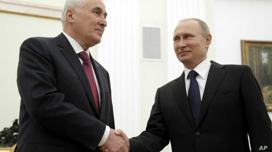 Russian President Vladimir Putin, right, and the leader of Georgia's breakaway province of South Ossetia Leonid Tibilov shake hands during their meeting in the Kremlin in Moscow, Russia, March 18, 2015.