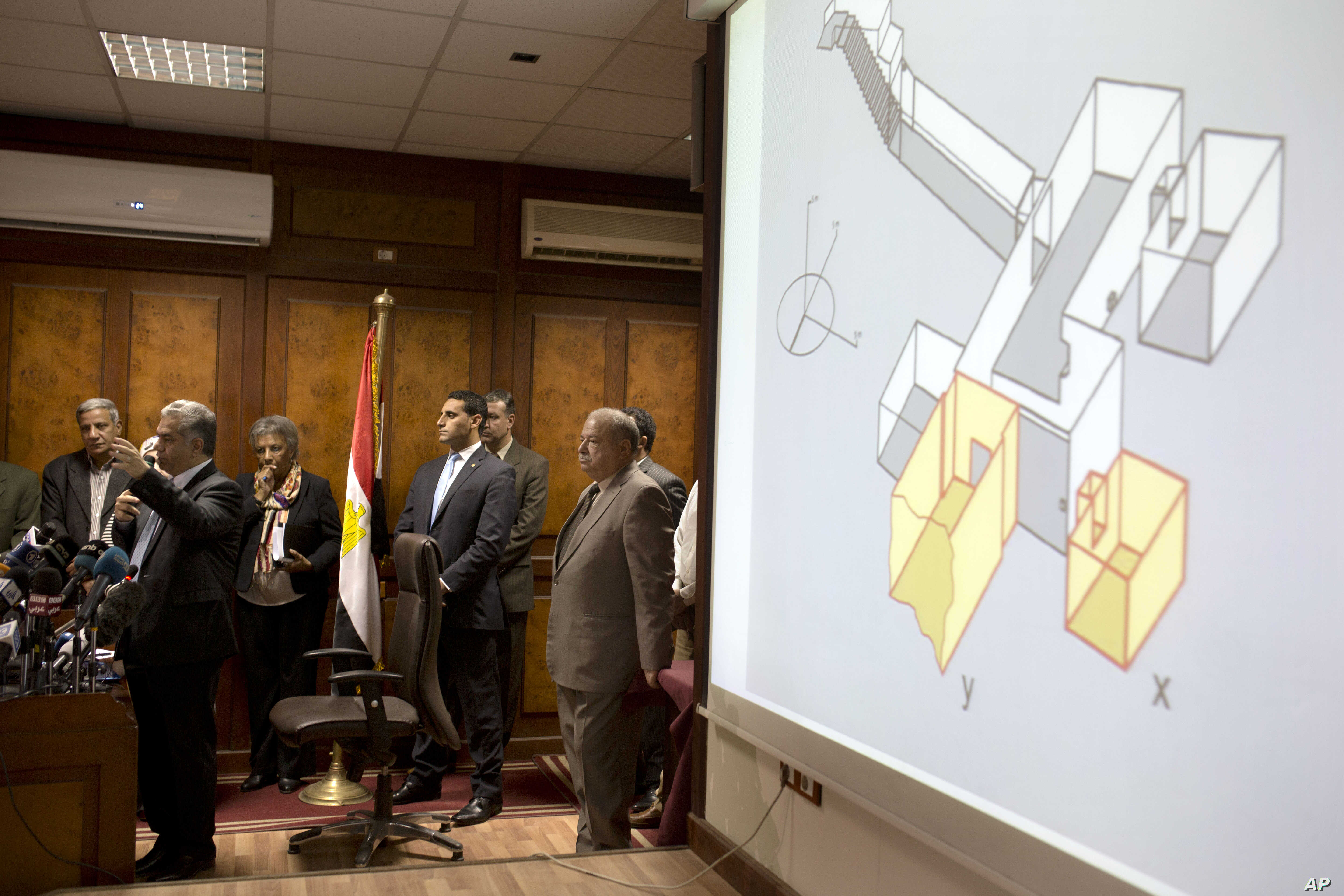 Egypt's Antiquities Minister Mamdouh el-Damaty, left, speaks during a press conference as he displays images of radar scans to King Tut's burial chamber on a projector, at the antiquities ministry in Cairo, Egypt, March 17, 2016.