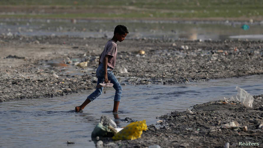 A boy crosses a drain on the banks of the river Ganges in Kanpur, India, April 4, 2017.