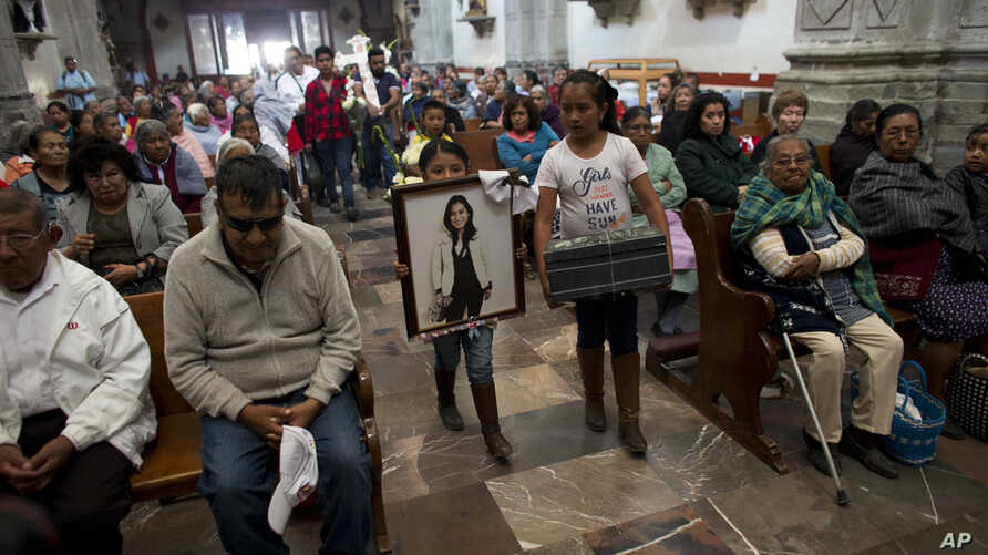 Relatives of murdered doctor and mother, Jessica Sevilla Pedraza, carry a framed portrait of her, a cross, and a box of mementos to be buried alongside her grave, as they arrive for Mass in Villa Cuauhtemoc, Mexico state, Aug. 18, 2017.
