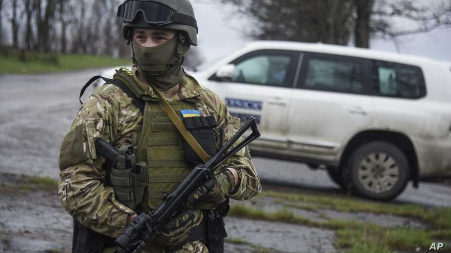 FILE - A Ukrainian soldier guards OSCE observers near the village of Shyrokyne, eastern Ukraine, April 19, 2015.