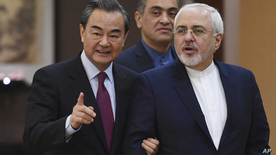 """Iranian Foreign Minister Mohammad Javad Zarif (R) arrives with Chinese Foreign Minister Wang Yi for a joint press conference in Beijing, China, Dec. 5, 2016. Zarif said that nations party to the Iran nuclear deal """"have the obligation to fully impleme"""