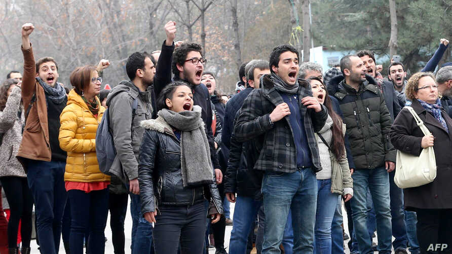 FILE - University students and academics react toward Turkish policemen at the Cebeci campus of Ankara University during a protest in Ankara, Feb. 10, 2017, against the dismissal of academics from universities following a post-coup emergency decree.