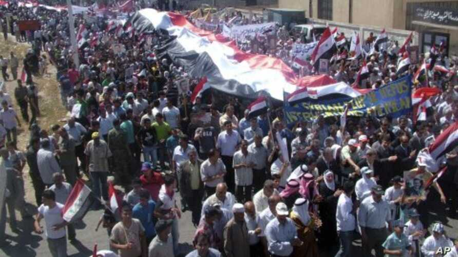 In this photo released by the Syrian official news agency SANA, Syrian pro-government protesters carry national flags along with pictures of Syrian President Bashar Assad during a rally in support of the reform program in the border town of Quneitra,