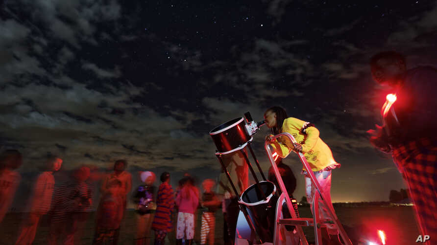 A student looks up at the moon through a telescope, during a visit by The Traveling Telescope to show students the science of astronomy, at St Andrew's School near Molo in Kenya's Rift Valley, Feb. 3, 2017.