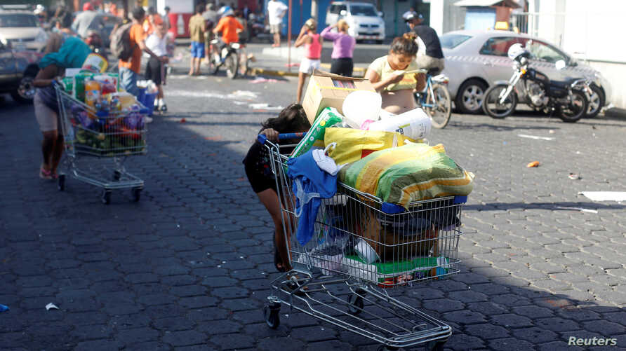 People with goods looted from a store walk pushing a shopping cart along a street after a protest over a controversial pension reform plan, in Managua, Nicaragua, April 22, 2018.