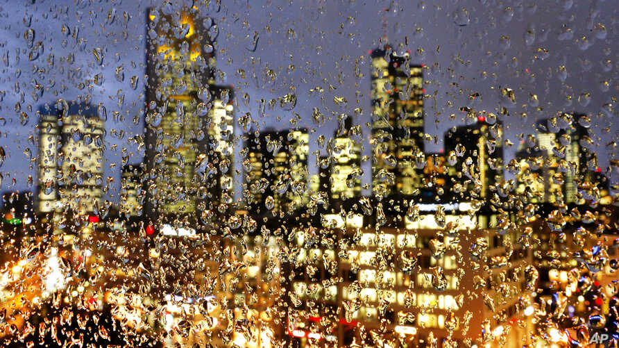 FILE - Buildings of the banking district are seen through rain drops on a glass railing in central Frankfurt, Germany, Jan. 11, 2017.