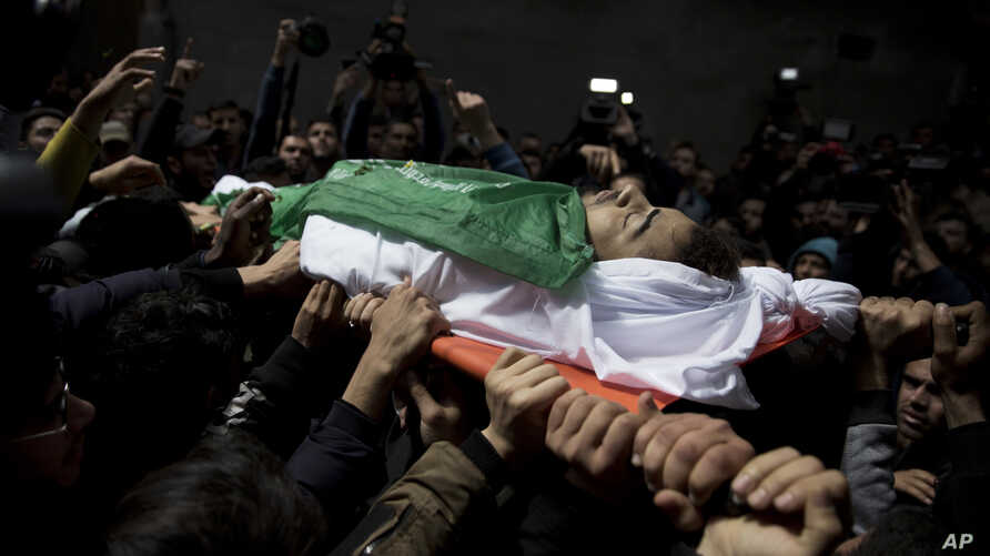Palestinians carry the body of Tamir Abu al-Khair, 17, who was shot and killed on Saturday by Israeli troops during a protest next to the Israeli border, eastern Gaza Strip, out of the family home during his funeral in Gaza City, Sunday, March 31, 20