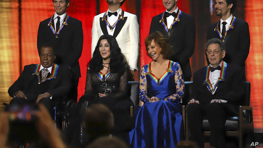 """2018 Kennedy Center honorees, front row from left, Wayne Shorter, Cher, Reba McEntire and Philip Glass; back row from left, the co-creators of """"Hamilton,"""" Thomas Kail, Lin-Manuel Miranda, Andy Blankenbuehler and Alex Lacamoire appear on stage during"""