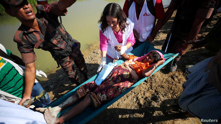 A pregnant Rohingya refugee who is in labor, is brought to a medical center on a stretcher after crossing the Bangladesh-Myanmar border in Palong Khali, near Cox's Bazar, Bangladesh, Nov. 3, 2017.