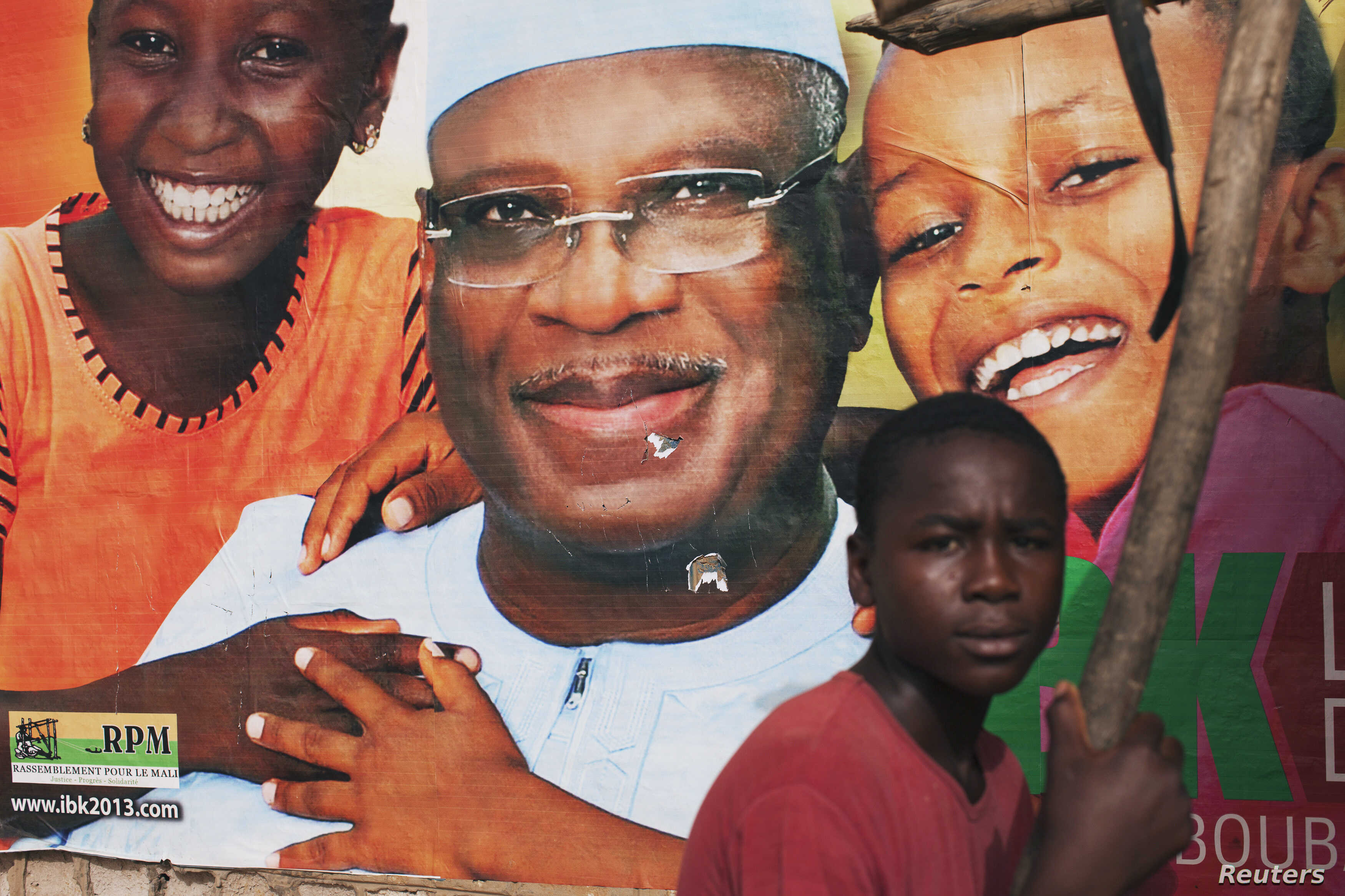 A boy sits in front of an electoral campaign poster for Malian presidential candidate Ibrahim Boubacar Keita, in Timbuktu, Mali, July 25, 2013.