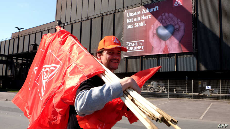 """A steelworker carrying flags by German metalworkers' union IG Metall walks past a banner reading """"Our future has a heart of steel"""" during a protest of steelworkers against European policies on April 11, 2016 in Duisburg, western Germany."""