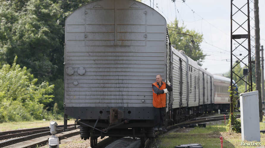 A guard rides on a train carrying the remains of victims of Malaysia Airlines MH17 downed over rebel-held territory in eastern Ukraine as it arrives in the city of Kharkiv, eastern Ukraine, July 22, 2014.