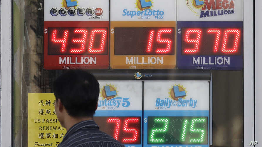 A man walks past Mega Millions and other lottery displays outside of The Lucky Spot in San Francisco, Oct. 18, 2018. The Mega Millions jackpot has climbed to $970 million, inching ever-closer to the $1 billion mark.