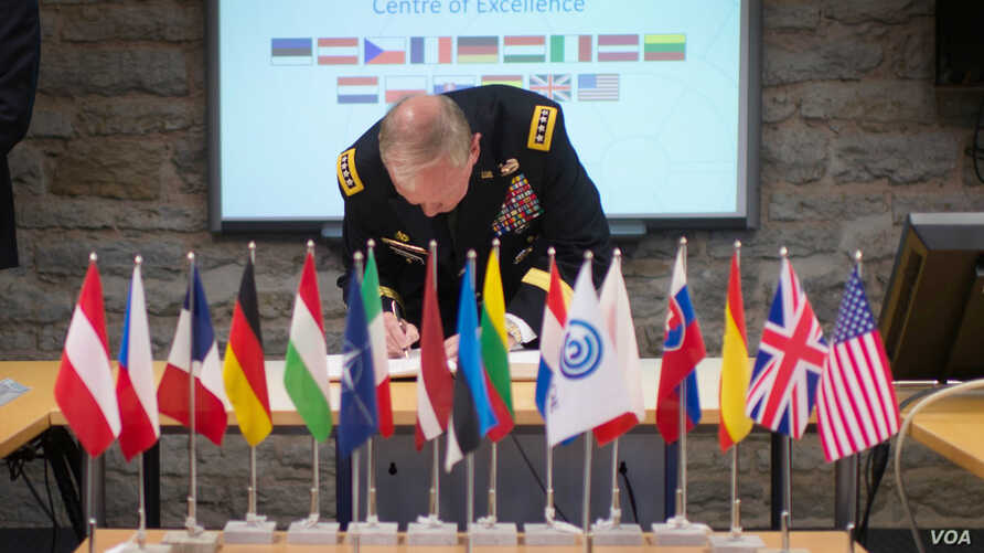 FILE - Gen. Martin E. Dempsey, chairman of the Joint Chiefs of Staff, signs a guestbook prior to starting a meeting at the NATO Cyber Defense Center of Excellence in Tallinn, Estonia, Sep. 14, 2015. (DoD photo by D. Myles Cullen/Released)