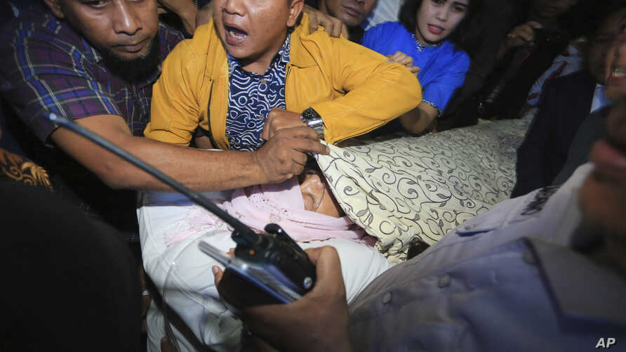 Aides use a blanket to cover Indonesian House Speaker Setya Novanto who lies on a stretcher as he is transferred to Cipto Mangunkusumo Hospital in Jakarta, Indonesia, Nov. 17, 2017.