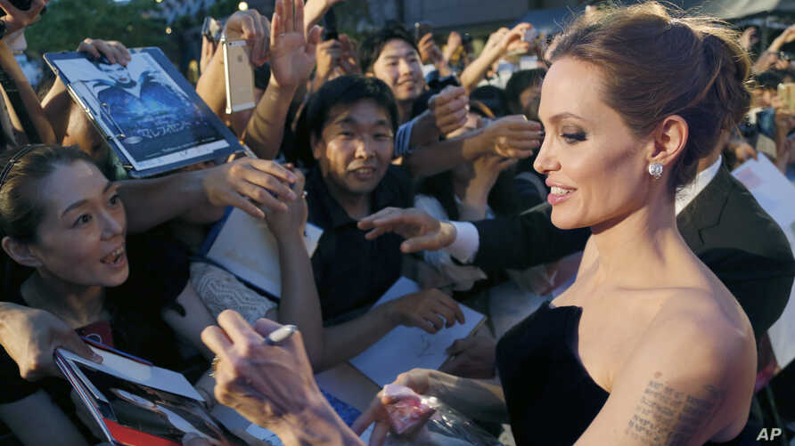 "FILE - Angelina Jolie, soon to direct a film about Kenyan icon Richard Leakey, greets fans at the Tokyo premiere of ""Maleficent,"" June 23, 2014."