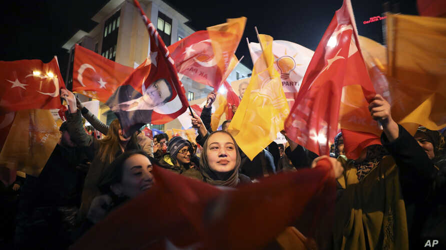 Supporters of President Recep Tayyip Erdogan wave flags in Istanbul, Sunday, March 31, 2019.