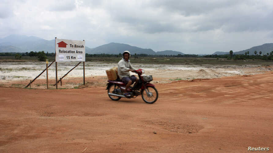 FILE - A motorcyclist rides past a dirt road at a site for a billion-dollar industrial estate in Dawei district, Myanmar, May 10, 2012.
