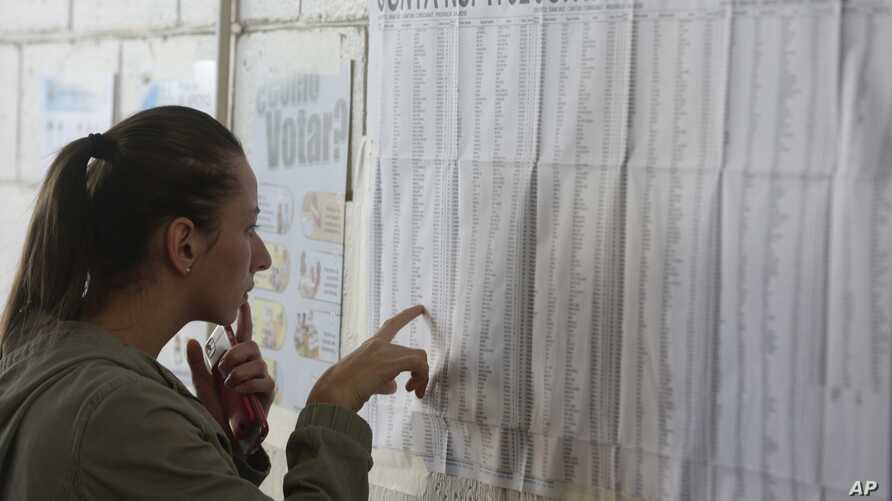 A woman scrolls the electoral list in search of her voting table location during the presidential election in San Jose, Costa Rica,  Feb. 4, 2018. Costa Ricans voted Sunday in a presidential race shaken by an international court ruling saying the cou
