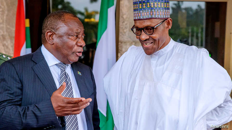 South Africa's President Cyril Ramaphosa speaks to Nigeria's President Muhammadu Buhari (R) at the State House in Abuja, Nigeria, July 11, 2018.