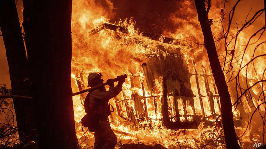 FILE - In this Nov. 9, 2018, photo, firefighter Jose Corona sprays water as flames from the Camp Fire consume a home in Magalia, Calif. A massive new federal report warns that extreme weather disasters, like California's wildfires and 2018's hurrican