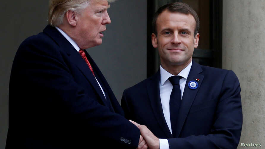 FILE - French President Emmanuel Macron shakes hands with U.S. President Donald Trump at the Elysee Palace on the eve of the commemoration ceremony for Armistice Day, 100 years after the end of the WWI, in Paris, Nov. 10, 2018.