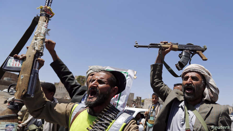 Shi'ite rebels wave their weapons at a checkpoint they erected on a street in Sanaa, Sept. 21, 2014.