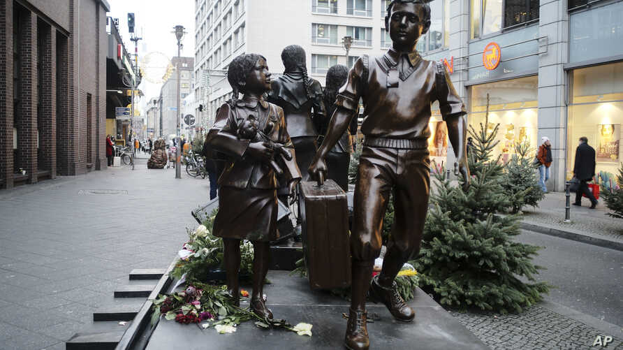 People pass a commemorative memorial statue to perpetuating the memory of the 'Kindertransport' (children transport) near Friedrichstrasse train station in central in Berlin, Germany, Dec. 17, 2018.