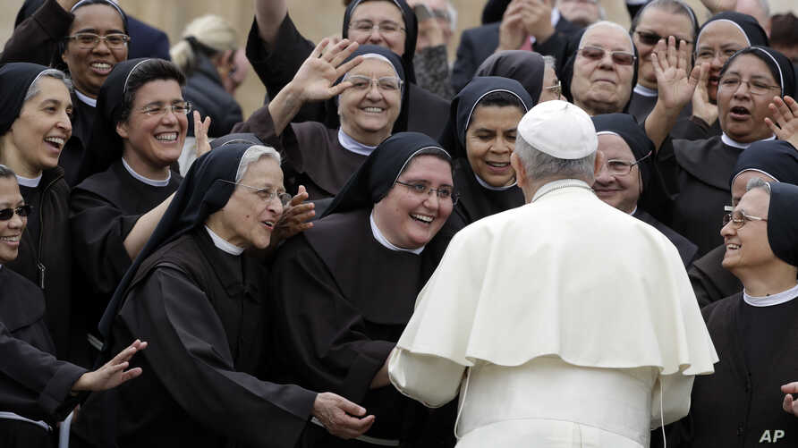 FILE - Pope Francis meets a group of Franciscan nuns during his weekly general audience, in St. Peter's Square, at the Vatican, Wednesday, May 9, 2018.