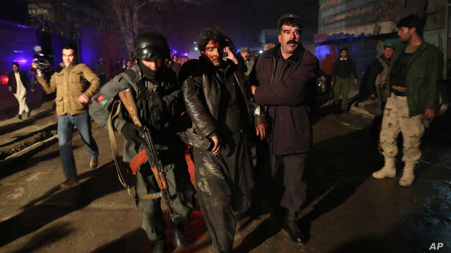 Afghan security forces assist an injured man at the site of an explosion in Kabul, Afghanistan, Jan. 17, 2014.