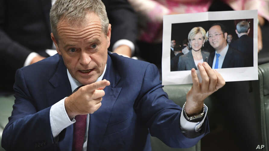 Leader of the opposition party Bill Shorten holds a photograph of Minister for Foreign Affairs Julie Bishop and Chinese businessman Huang Xiangmo, June 14, 2017, in Canberra, Australia. Australia has canceled the residency of Huang but the foreign mi