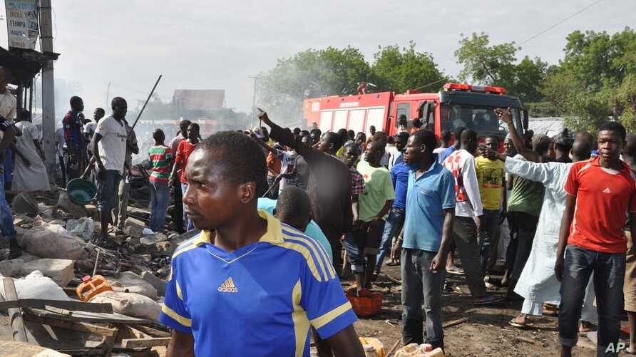 People gather at the scene of a car bomb explosion, at the central market, in Maiduguri, Nigeria, July 1, 2014. They immediately blamed Boko Haram, the Islamic extremist group, whose birthplace is Maiduguri.