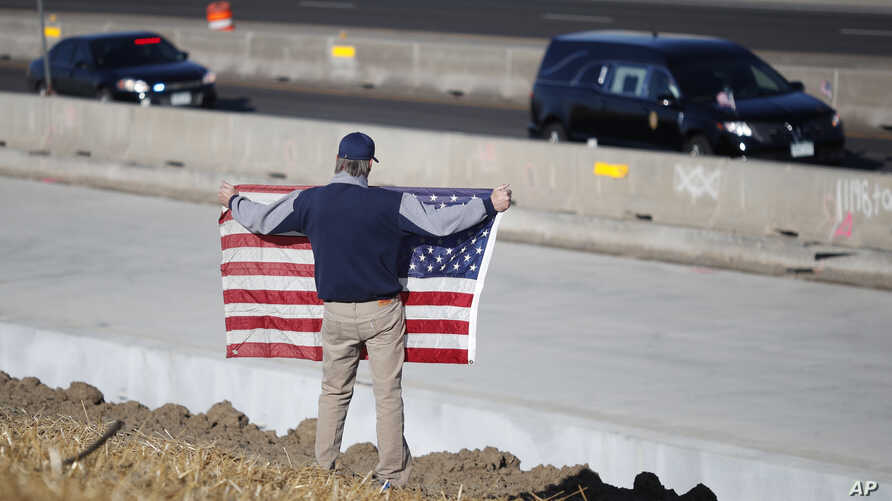 David Morgan of Highlands Ranch, Colo., holds an American flag as a procession of law enforcement vehicles accompany a hearse carrying the body of a sheriff's deputy shot and killed while responding to a domestic disturbance, Dec. 31, 2017, in Highla